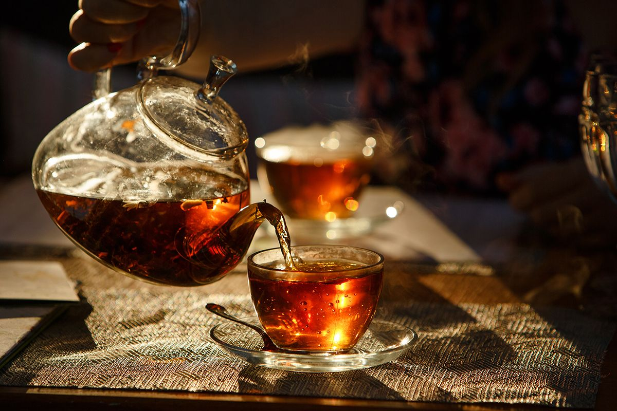 Image of a glass teapot on a wooden bench.